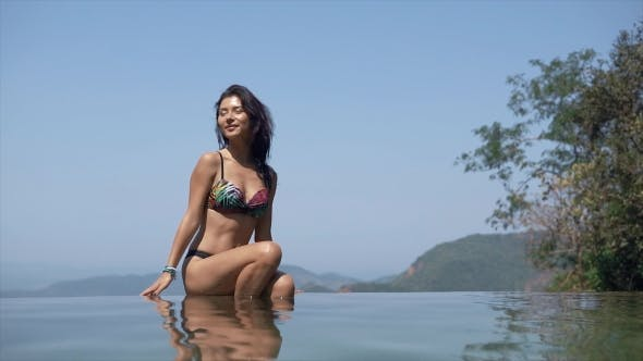 Thumbnail for Happy Girl Sitting on the Edge of the Pool
