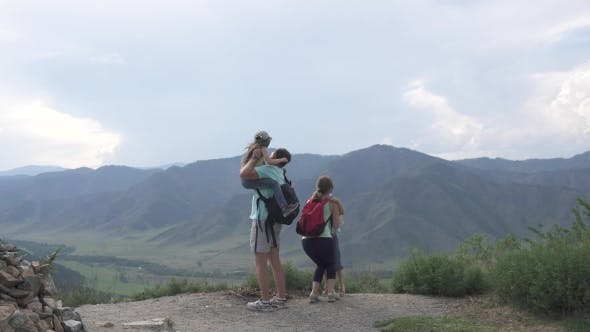 Thumbnail for Family of Tourists. Parents Hold Their Children in Their Arms and Show Them a Beautiful View of the