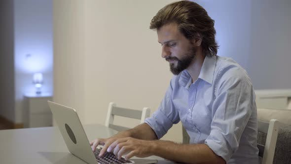 Thumbnail for Concentrated Young Man with Beard Typing on Laptop at Table
