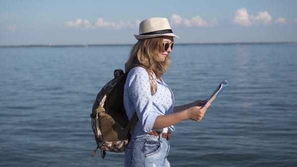 Thumbnail for Girl Traveler Holding a Map. Young Woman Tourist Is on the Beach. Girl Hipster with a Backpack