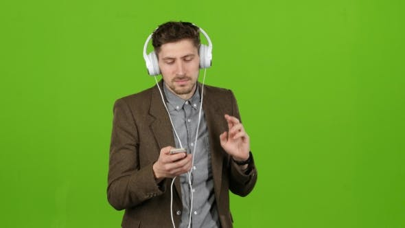 Thumbnail for Guy Listens To Music Through Headphones, Dances and Sings. Green Screen