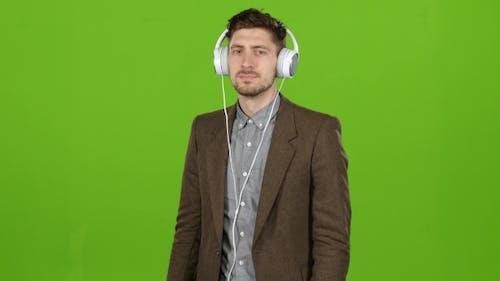 Boy Businessman Listens To Quiet Music in Headphones. Green Screen