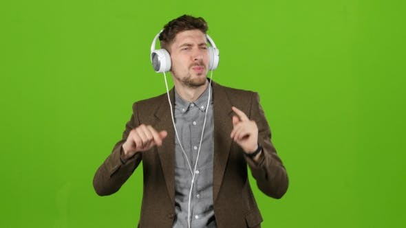 Thumbnail for Guy Listens To Energetic Music in Headphones and Dances. Green Screen