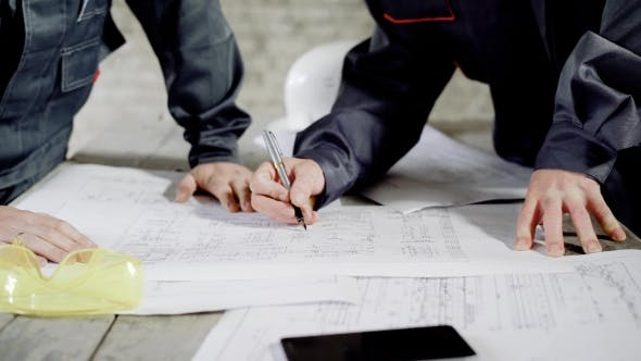 Thumbnail for Crop Men Working with Blueprint. Crop Faceless Shot of Men Working at Table with Blueprint and