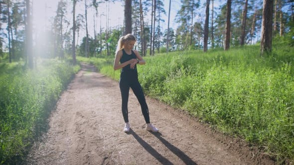 Thumbnail for Girl Checking Time and Pulse on Pathway in Summer Forest