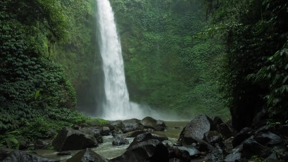 Thumbnail for Amazing Nungnung Waterfall, Slow Motioned Falling Water Hitting Water Surface, Some Huge Rocks