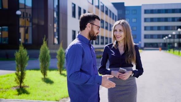 Thumbnail for Two Entrepreneurs Smiling and Talking. Male and Female Cheerful Business People Communicating and