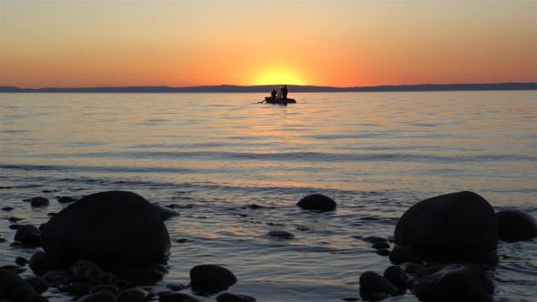 Thumbnail for Silhouette of Men in Boat at Sunset Against Bright Golden Sun and Red Sky