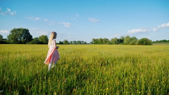 Cover Image for A 6 Year Old Girl in a Pink Dress Walking Across the Field with Yellow Flowers