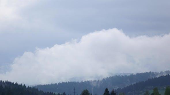 Thumbnail for Wolken bilden sich über Wald auf Hängen von Hügeln,