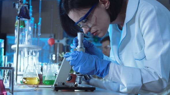 Thumbnail for Young Female Scientist Looking Down a Microscope