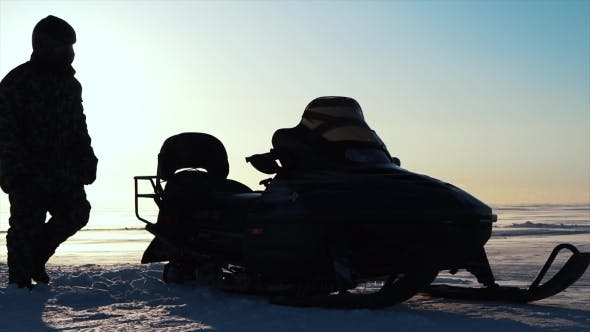 Thumbnail for Man Driving Scooter Snowmobile in Cold Winter