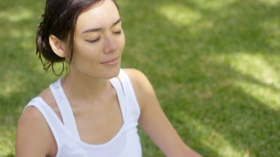 Thumbnail for Serene Young Woman Meditating on a Green Lawn