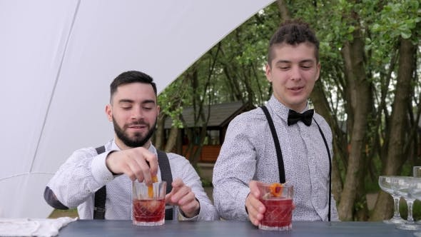 Thumbnail for Smiling Bartenders Behind Bar, Barman Making Cool Drink in Glass, Bartender Decorate Cocktails