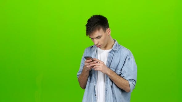 Thumbnail for Man Looks at the Phone in the Photo, and Has Fun. Green Screen