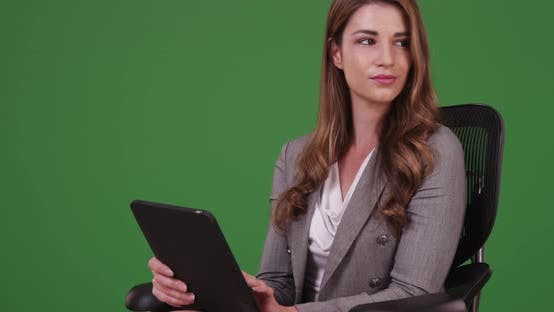 Thumbnail for Businesswoman in her 20s using tablet while sitting on green screen
