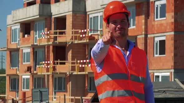 Thumbnail for Construction Worker Points To the Camera and Agrees in Front of Building Site