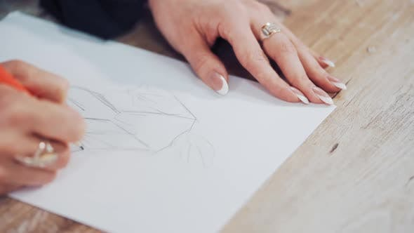 Young woman's hands of a fashion designer drawing sketches of clothes in the atelier.