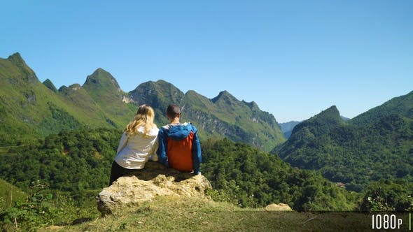 Hiking Couple Sit Down and Enjoy the Beautiful Mountain Scenery