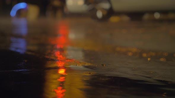 Nieselregen und Pfützen auf dem Asphalt mit Lichtreflektion