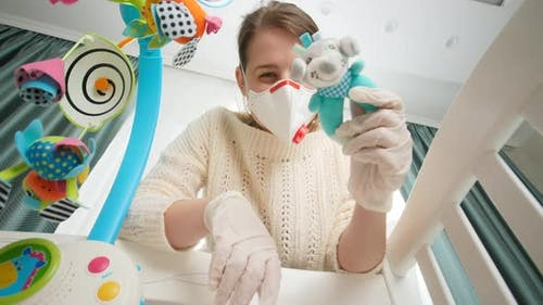 Mother in Medical Respirator Mask Playing Toys with Her Baby Lying in Bed