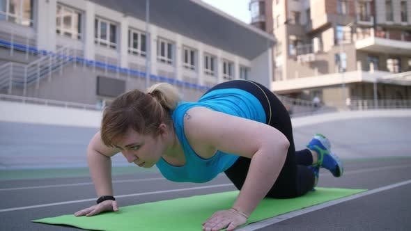 Thumbnail for Plus Size Female Doing Push-ups on Sports Ground