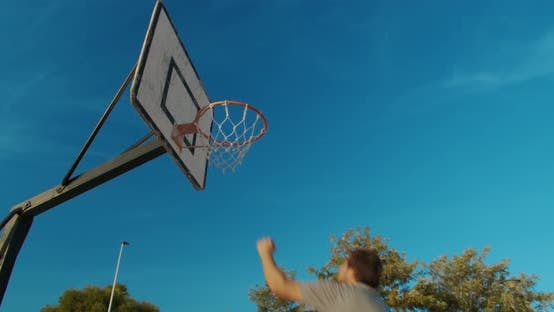 Thumbnail for Male Basketball Player Slam Dunking on an Outdoor Basketball Court
