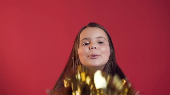 Thumbnail for Adorable Cheerful Little Girl with Braces Blowing Golden Confetti to the Camera