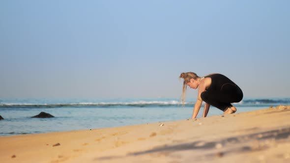 Thumbnail for Blonde Girl in Black Tracksuit Practices Yoga on Ocean Beach