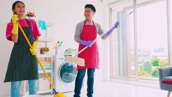 Husband and wife having fun while cleaning their room.