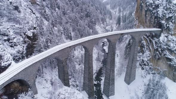 Thumbnail for Landwasser Viaduct with Railway at Winter Snowy Day in Switzerland. Aerial View. Swiss Alps. Snowing