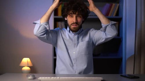 POV Shot of Unhappy Young Man Having Idea Moment Pointing Finger Up While Sitting at Desk