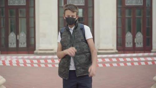 Happy Boy in Covid-19 Gesichtsmaske Tanzen vor der geschlossenen Schule und zeigen Siegesgesgestik