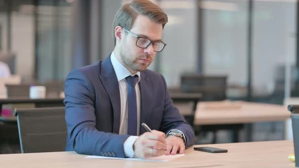 Pensive Businessman Writing on Paper, Thinking