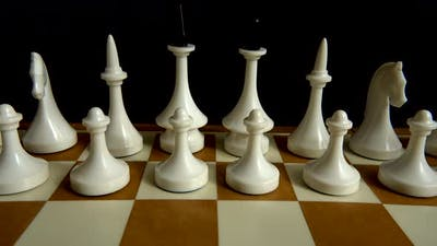 Chess on a chessboard. Shooting on a black background.