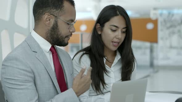 Cover Image for Business Colleagues with Laptop and Papers