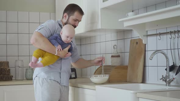 Man With Boy On Hands Cooking