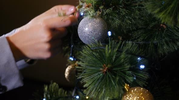 Weihnachtszeit und Happy New Year-Symbole. Frau schmückt Weihnachtsbaum mit Bällen und Spielzeug