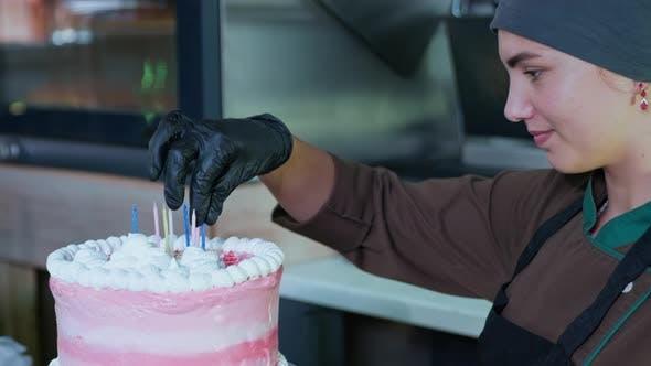 Thumbnail for Schöne weibliche Bäckerin schmückt festliche Kuchen mit Kerzen für Glückwunsch Besucher im Café