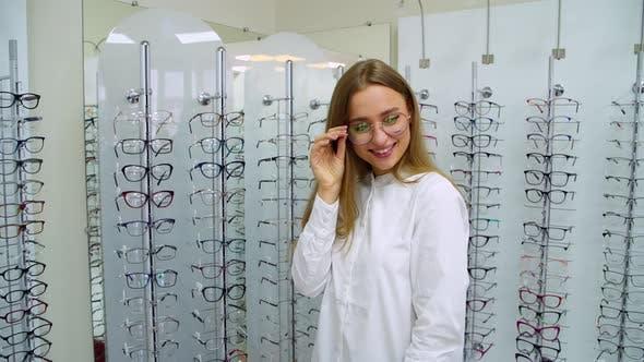 Thumbnail for Woman in optics store. Happy woman choosing glasses at optics store