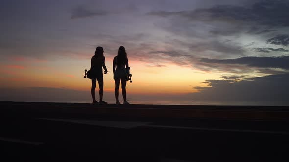 Cover Image for Two Girls Standing on the Edge of the Road with Skateboards in Their Hands Watching the Sunset