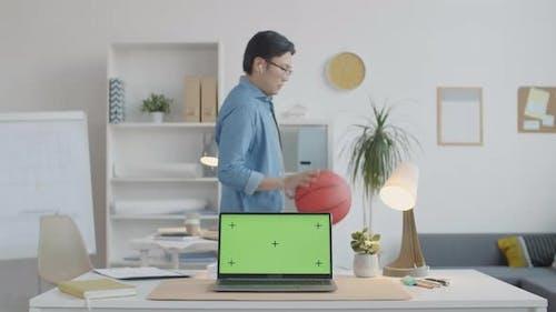 Asian Man Dribbling Basketball in Office