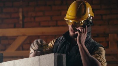 Man Answering Phone Call on Construction Site