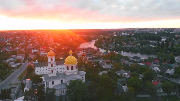 Cover Image for Small Church at the Bright Cloudy Sunset Filmed By Drone in Small European City. Kyiv Region