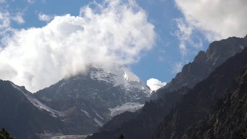 View of High Snowy Mountains with Clouds in the Sky.