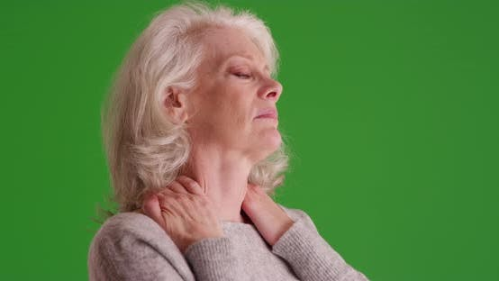 Thumbnail for Close up of elder woman with sore neck on greenscreen