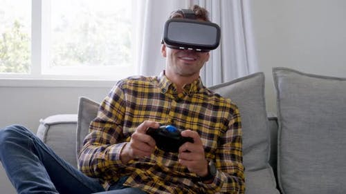 Young man using virtual reality headset and playing video game at home 4k