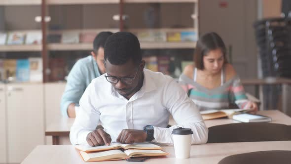 Thumbnail for African American Male College Studen Preparing for Exams in the Library.
