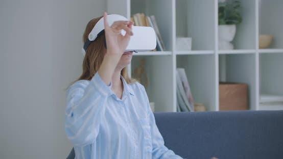 Thumbnail for Junge fröhliche Frau trägt Virtual Reality Headset Ansehen 360 VR Video Film Sitzen im Bett