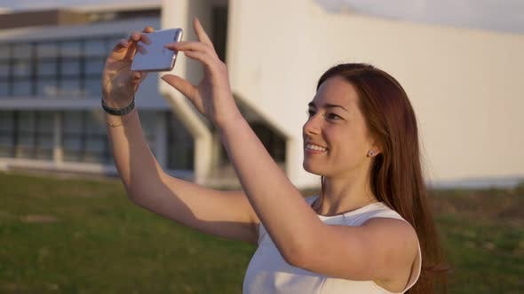 Thumbnail for Beautiful Young Woman with Long Hair Taking Selfie During Sunset